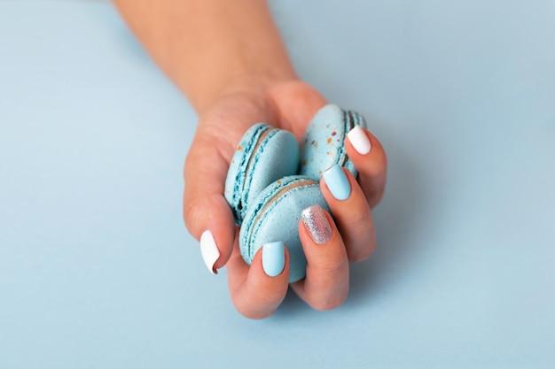 Main féminine avec des ongles de manucure bleus tenant des macarons sucrés