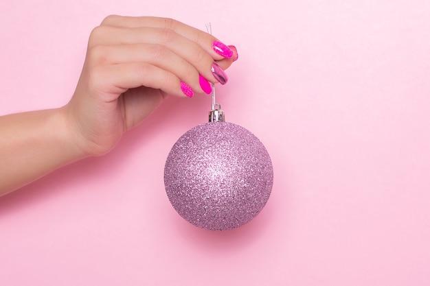 Main féminine avec des ongles de manucure festive tenant le jouet de noël