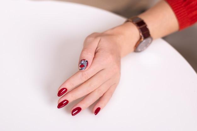 Main féminine avec des ongles de manucure rouges