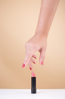 Main féminine avec des ongles rouges prenant le rouge à lèvres