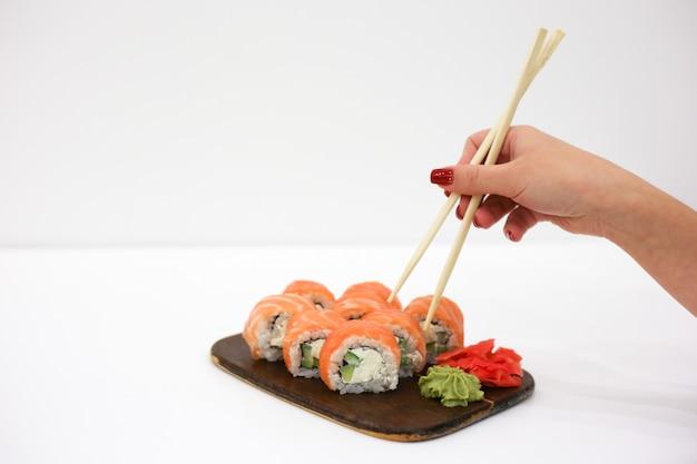 Une main féminine avec des ongles rouges prend le rouleau de philadelphie avec des baguettes. nourriture japonaise. place pour le texte