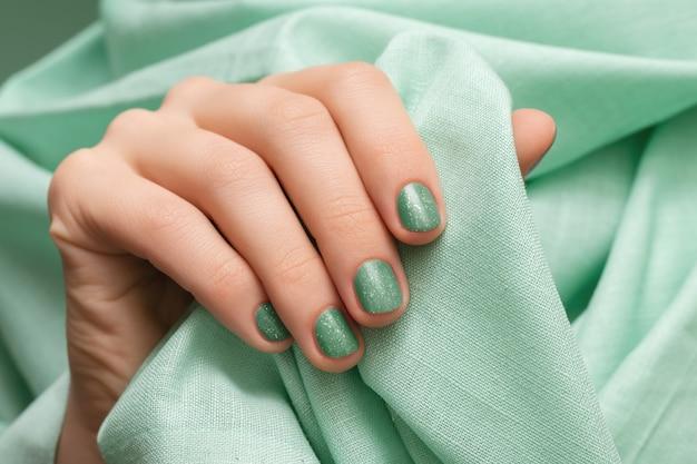 Main féminine avec des ongles verts scintillants