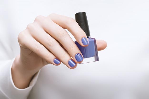 Main féminine avec des ongles violets tenant une bouteille de vernis à ongles
