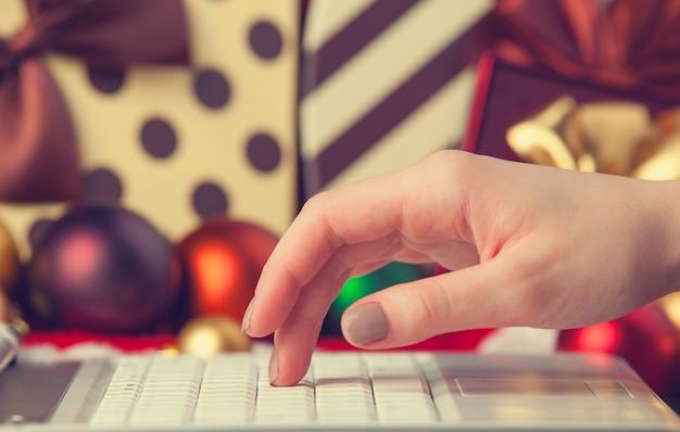 Main féminine d'ordinateur et cadeaux de noël à l'arrière-plan