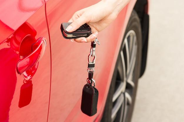 Une main féminine ouvre la porte d'une voiture rouge