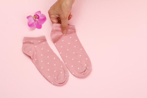 Main féminine et paire de chaussettes pour femmes, fleur d'orchidée sur fond rose, vue de dessus avec espace de copie.