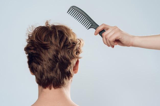 Main féminine peigne les cheveux de l'homme aux cheveux roux vue de dos