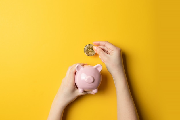 Main féminine avec pièce de monnaie bitcoin mise dans une tirelire