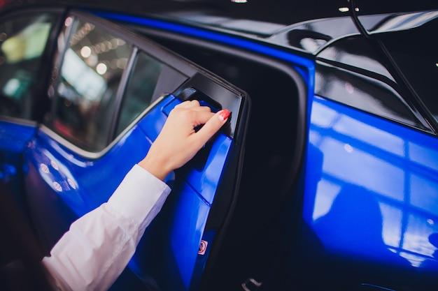 Main féminine pour insérer la porte ouverte de la voiture arrière. pour le transport et l'image automobile