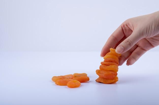 Main féminine prenant abricot séché sur blanc.