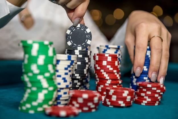 Main féminine prenant des jetons de poker de pile