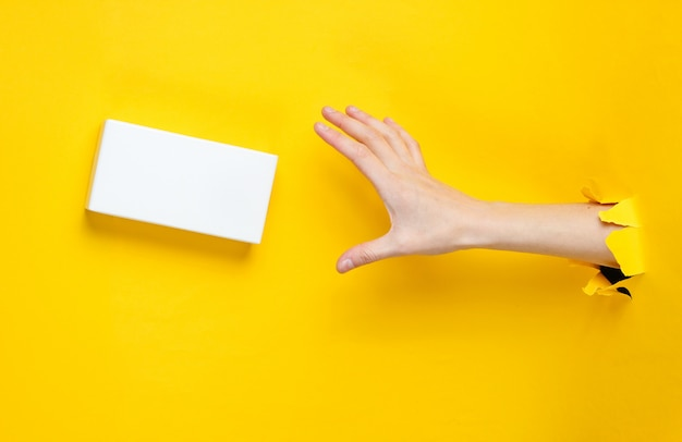 La main féminine prend une boîte blanche à travers du papier jaune déchiré. concept de mode créative minimaliste