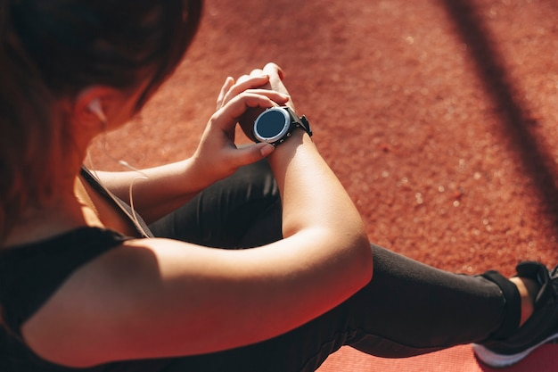 Main féminine regardant sa montre de sport après avoir fait du cardio pour perdre le port en plein air dans un parc de sport tout en se reposant sur le sol le matin.