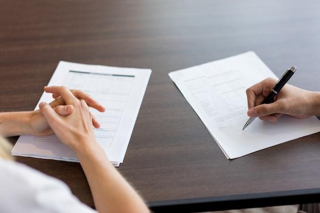Main féminine remplissant un questionnaire pour un candidat masculin.