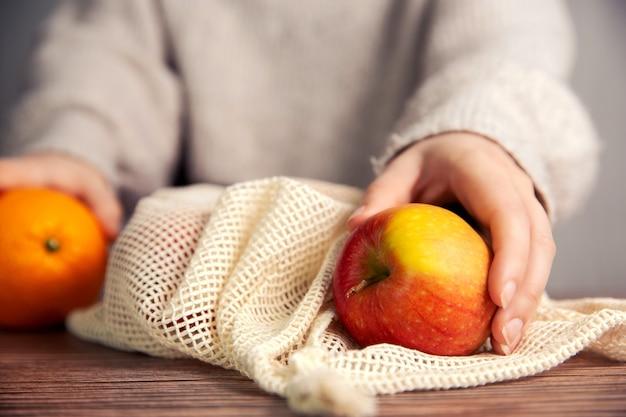 Main féminine avec sac en filet écologique pour faire les courses avec des fruits frais