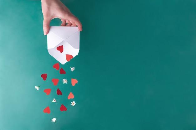 Main féminine secouant les coeurs rouges et les fleurs blanches d'une enveloppe blanche. la saint-valentin.