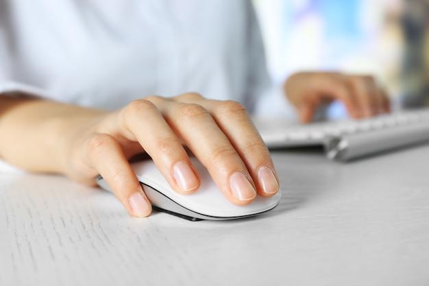 Main féminine avec souris d'ordinateur sur table