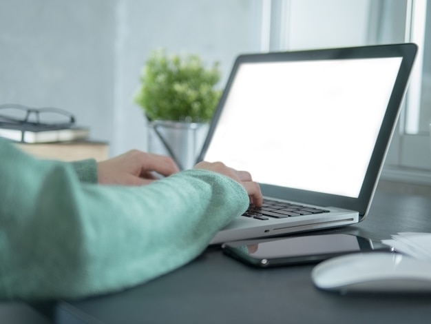 Main féminine tapant sur un ordinateur portable avec clavier avec écran vide sur le bureau
