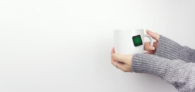 Main féminine avec une tasse bleue sur fond blanc. vue recadrée. espace de copie.