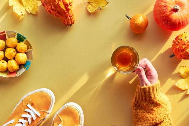 Main féminine avec tasse de thé, citrouilles orange et assiette en papier avec coing, copy-space