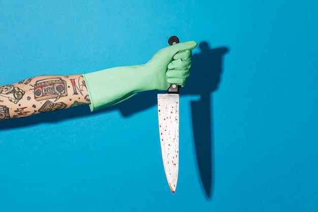 Main féminine tatouée dans un gant tenant un couteau