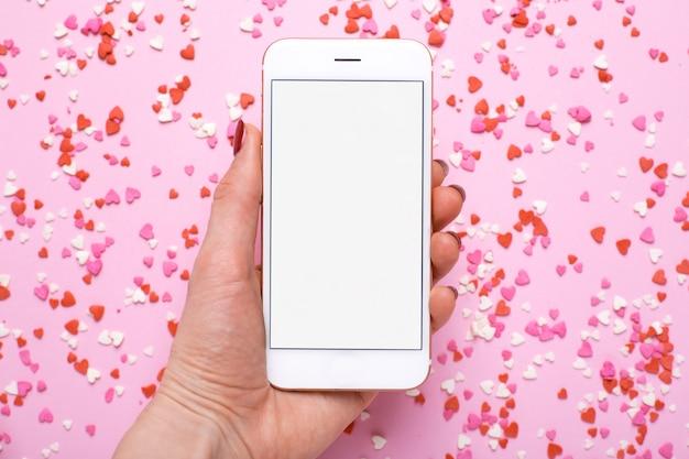 Main féminine avec téléphone portable avec des coeurs roses et rouges