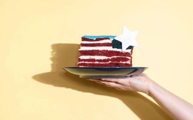 Main féminine tenant une assiette avec un morceau de gâteau sous la forme du drapeau des états-unis sur fond jaune, célébrant le jour de l'indépendance, en gros plan.