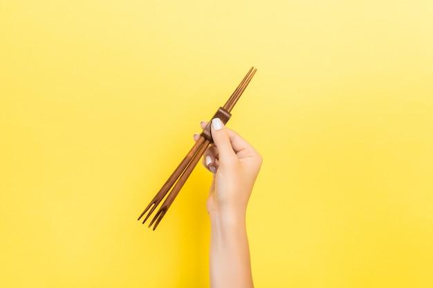 Main féminine tenant des baguettes. concept de sushi avec espace vide