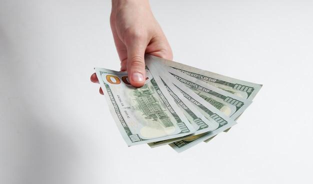 Main féminine tenant des billets de cent dollars sur blanc.