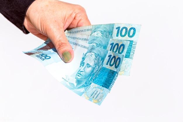 Main féminine tenant des billets de cent dollars sur une surface blanche isolée