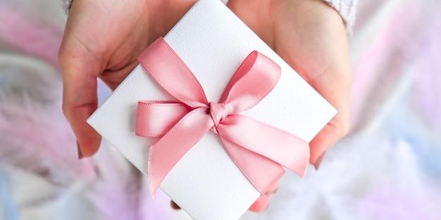 Main féminine tenant une boîte cadeau blanche avec un ruban rose sur fond de texture de soie blanche. plume d'oiseau colorée. notion de vacances. cadeau pour la saint-valentin anniversaire des mères fête des femmes