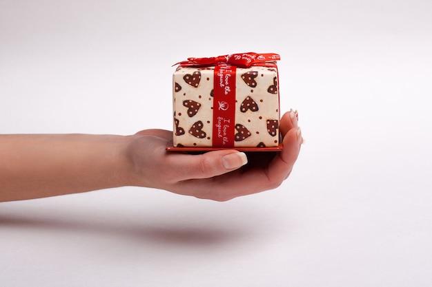 Main féminine tenant une boîte-cadeau