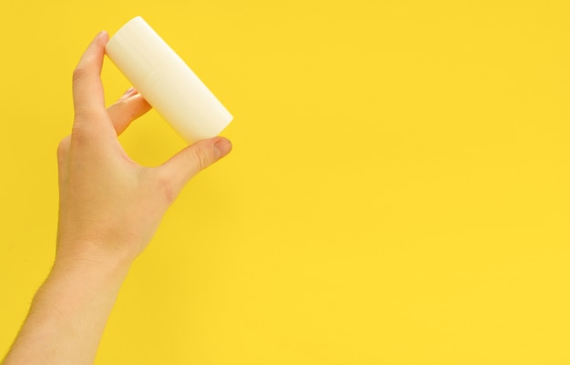 Main féminine tenant une bouteille cosmétique blanche sur fond jaune mock up espace copie soins de la peau d'été co...