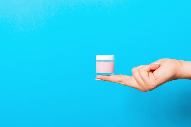 Main féminine tenant une bouteille de crème de lotion isolée. fille donne des produits cosmétiques jar sur bleu