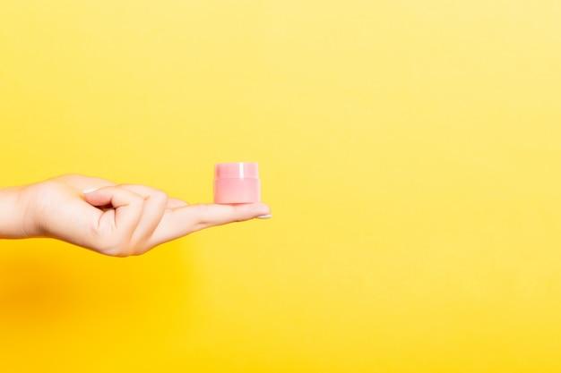Main féminine tenant une bouteille de crème de lotion isolée. fille donne des produits cosmétiques jar sur jaune