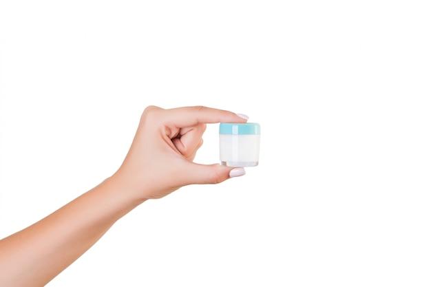 Main féminine tenant une bouteille de crème de lotion isolée. fille donne des produits cosmétiques de pot sur blanc