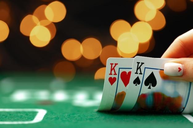 Main féminine tenant des cartes à jouer contre bokeh