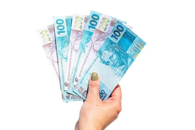Main féminine tenant cent deux cents factures de reais sur une surface blanche isolée, concept de paiement ou de prestation gouvernementale
