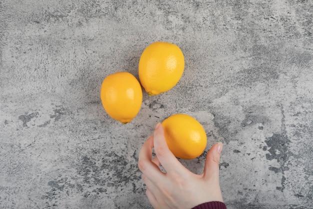 Main féminine tenant un citron jaune sur une table en pierre.