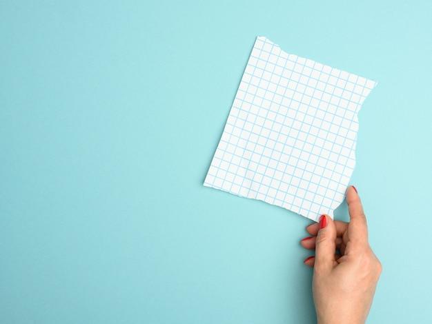 Main féminine tenant une feuille de papier vierge déchirée dans une cage sur fond bleu
