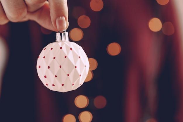 Main féminine tenant un fond festif de boule de noël