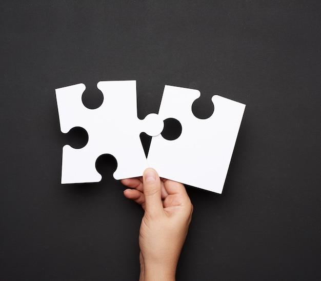 Main féminine tenant de gros morceaux de puzzles en papier