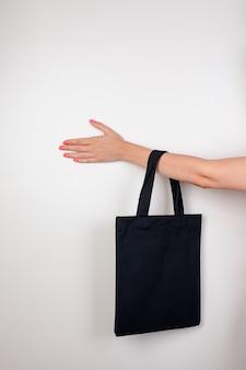 Main féminine tenant une maquette d'éco-sac de petit éco-sac réutilisable noir fait de matériaux recyclés sur fond blanc...