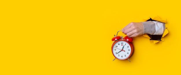 Main féminine tenant une montre rouge dans un trou sur fond jaune. bannière.