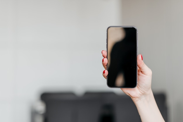 Main féminine tenant un nouveau téléphone avec copie espace vide écran vide à la maison dans l'appartement