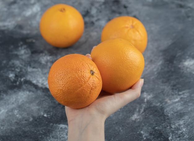 Main féminine tenant des oranges sur une table en marbre.