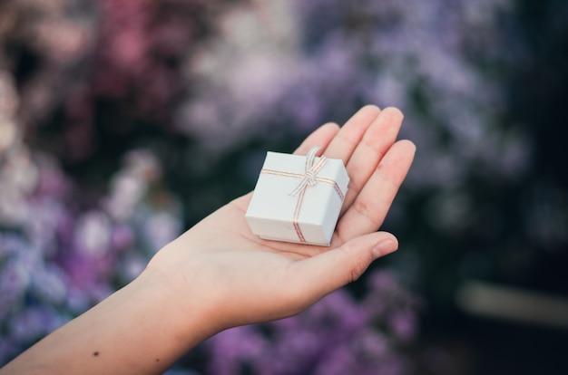 Main féminine tenant une petite boîte-cadeau