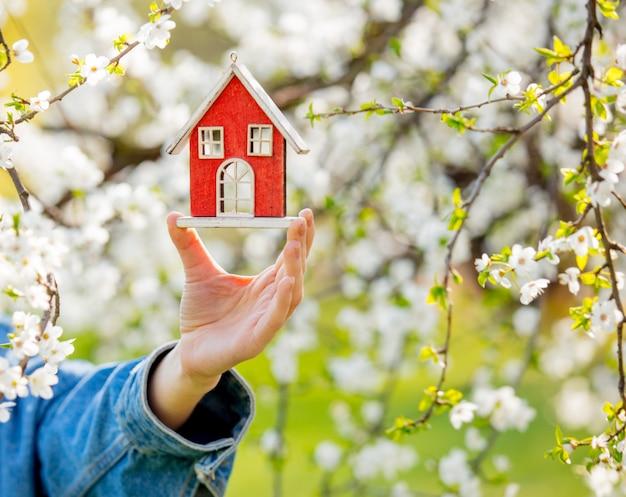 Main féminine tenant une petite maison rouge près d'un arbre en fleurs.