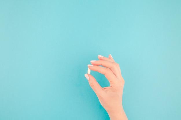 Main féminine tenant une pilule blanche