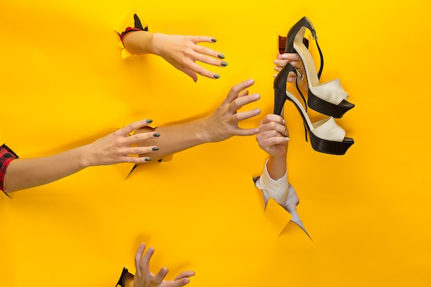 La main féminine tenant des sandales pour femmes à travers un papier déchiré isolé